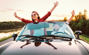 Pump up your Refinance Couple in car celebrating auto refinance